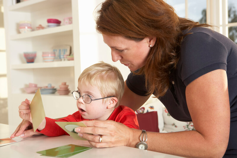 Therapist shows flashcards to child with down syndrom